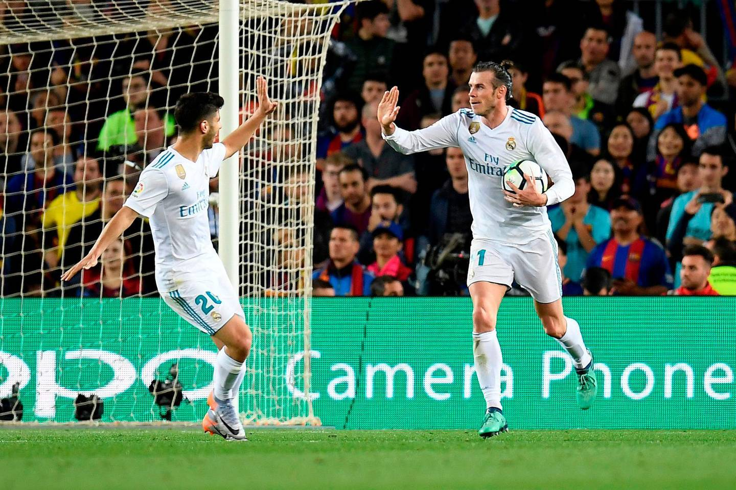 Real Madrid's Welsh forward Gareth Bale (R) celebrates with Real Madrid's Spanish midfielder Marco Asensio after scoring a goal during the Spanish league football match between FC Barcelona and Real Madrid CF at the Camp Nou stadium in Barcelona on May 6, 2018. / AFP PHOTO / LLUIS GENE