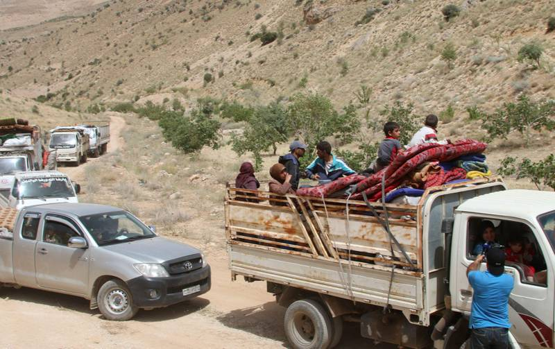 Syrian refugees ride vehicles in the Lebanese eastern border town of Arsal as they head towards the Syrian region of Qalamoun on July 12, 2017 as part of a deal that was negotiated by Syrian rebels in the camps and Lebanon's Hezbollah group. Around 300 Syrian refugees returned from camps near a restive border town in northeast Lebanon to their Syrian hometown, a security source and AFP correspondent said. / AFP PHOTO / STRINGER