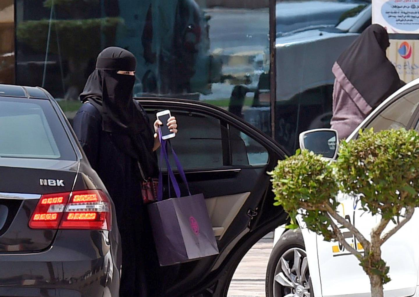 A Saudi woman disembarks from a car outside a mall in the Saudi capital Riyadh on September 27, 2017. Saudi Arabia will allow women to drive from next June, state media said on September 26, 2017 in a historic decision that makes the Gulf kingdom the last country in the world to permit women behind the wheel.  The shock announcement comes after a years-long resistance from women's rights activists, some of whom were jailed for defying the ban on female driving. / AFP PHOTO / FAYEZ NURELDINE