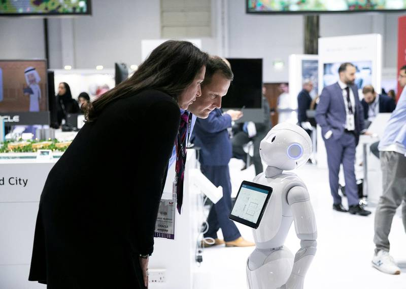 DUBAI, UNITED ARAB EMIRATES. 06 OCTOBER 2019. A man and a woman intercat with a robot at Oracle's booth during Gitex Technology Week at Dubai World Trade Center.(Photo: Reem Mohammed/The National)Reporter:Section: