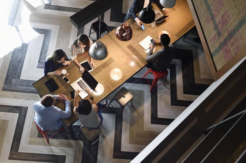 Young Chinese colleagues working together in a busy co-working space from above. Getty Images