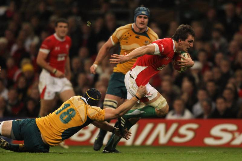 CARDIFF, WALES - NOVEMBER 28:  Sam Warburton of Wales bursts through the tackle of Mark Chisholm of Australia during the Invesco Perpetual Series match between Wales and Australia at the Millennium Stadium on November 28, 2009 in Cardiff, Wales.  (Photo by David Rogers/Getty Images)