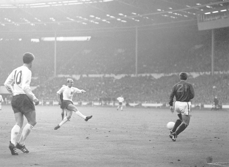 Bobby Charlton scores England's second goal as Portugal's Jose Carlos runs in to try and intercept during the World Cup semi-final match at Wembley, 27th July 1966. England won the match 2-1. (Photo by Central Press/Hulton Archive/Getty Images)