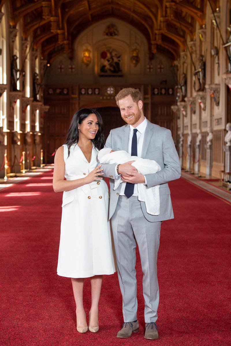 Britain's Prince Harry, Duke of Sussex (R), and his wife Meghan, Duchess of Sussex, pose for a photo with their newborn baby son in St George's Hall at Windsor Castle in Windsor, west of London on May 8, 2019. / AFP / POOL / Dominic Lipinski