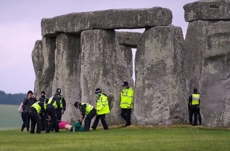 AMESBURY, ENGLAND - JUNE 21: People are removed by police officers after a crowd entered the closed site at Stonehenge on June 21, 2021, in Amesbury, United Kingdom. English Heritage, which manages the site, said, 'With this week's news that the Government is delaying the lifting of the remaining COVID-19 restrictions on 21 June we have taken the difficult decision to cancel the planned Summer Solstice celebrations at Stonehenge this year'. (Photo by Finnbarr Webster/Getty Images)