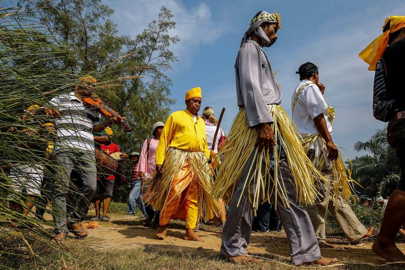 epa06546231 Members of Malaysia's Mahmeri tribe march along to the sea to pray for their ancestors during a thanksgiving ceremony in Pulau Carey, Kelang near Kuala Lumpur, Malaysia, 20 February 2018. The thanksgiving ceremony is to appease the sea spirits on the seabed of Malacca Straits during low tide. They marched from their village to the sea along with their shaman to perform ritual food offerings to seek blessing and protection of their seafaring ancestors.  EPA/AHMAD YUSNI