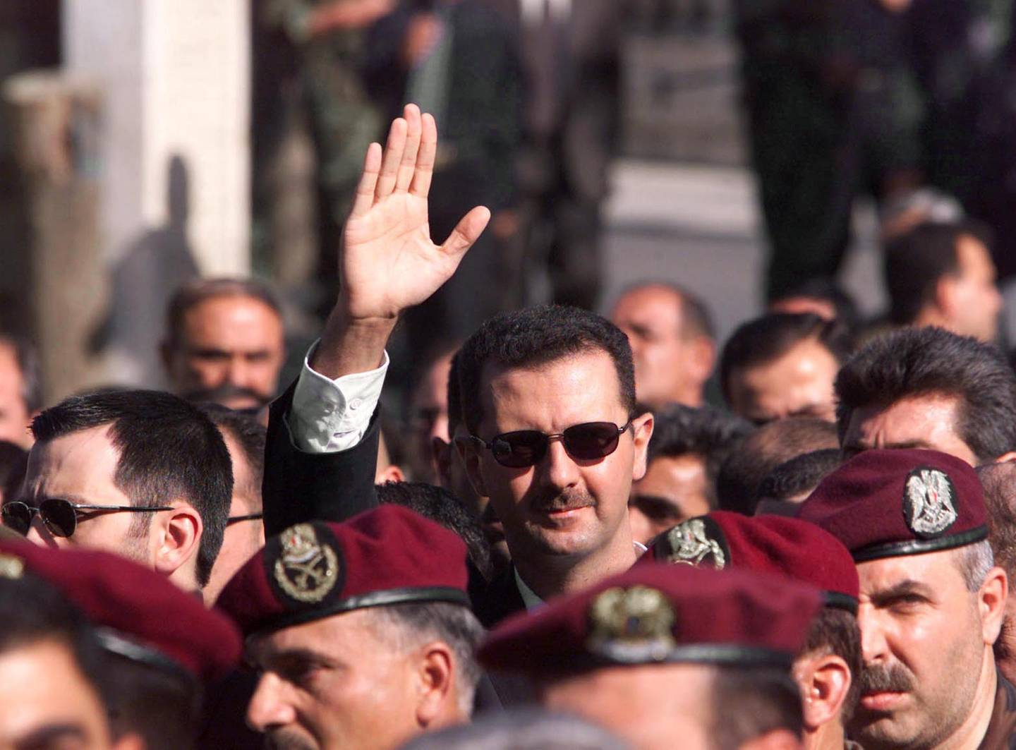 Syrian heir apparent Bashar al-Assad waves as he follows the funeral procession of his father President Hafez al-Assad in Damascus 13 June 2000. Assad, who ruled his country with n iron fist for 30 years, died 10 June at the age of 69. (ELECTRONIC IMAGE) (Photo by RABIH MOGHRABI / AFP)