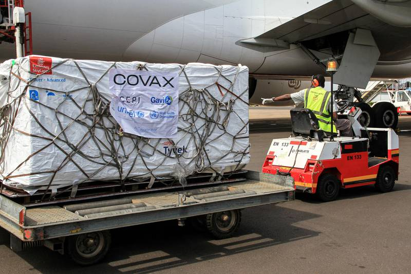 An employee unloads boxes of Oxford/AstraZeneca vaccines against the Covid-19 after their delivery as a part of the UN-led Covax initiative, which assists poorer countries to receive the medicine, at Entebbe international airport on March 5, 2021. - Uganda received a first batch of doses of the AstraZeneca drug and will start giving out the vaccine on March 10. (Photo by Tina SMOLE / AFP)