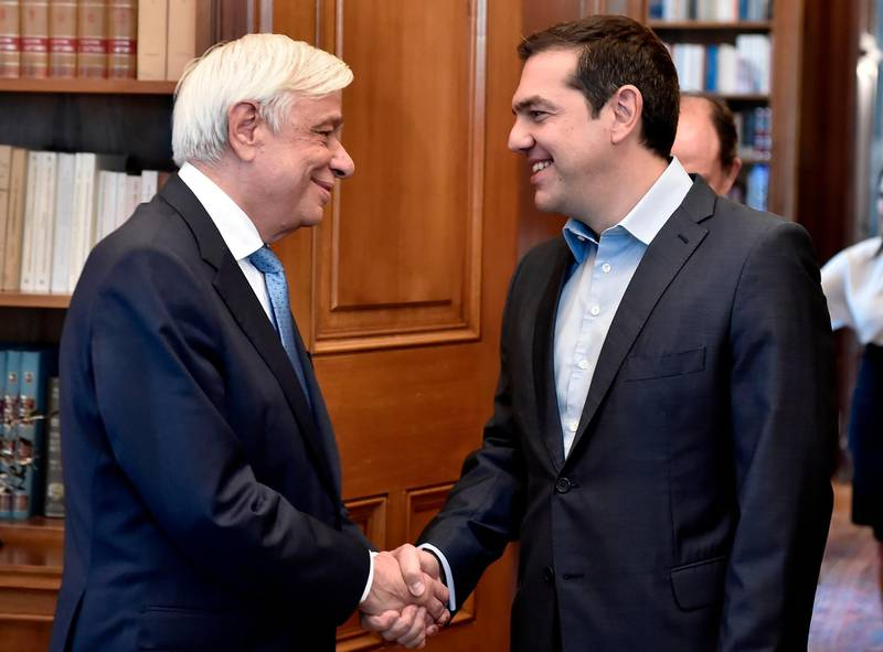 """Greek President Prokopis Pavlopoulos (L) shakes hands with Greek Prime Minister Alexis Tsipras at the Presidential Palace in Athens on June 22, 2018, following a decision by Eurozone financial ministers to complete the eight-year bailout program for Greece.  Greek Prime Minister Alexis Tsipras said the country was """"turning a page"""" after eurozone ministers declared its crisis over as they granted Athens debt relief under a bailout exit strategy. / AFP / Milos Bicanski"""