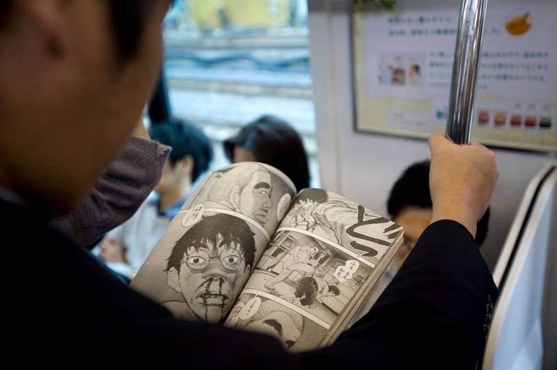 Man reading Manga comic book on railway train in Tokyo Japan *** Local Caption *** 3.B0R142
