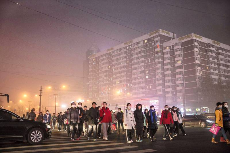 BEIJING, CHINA - DECEMBER 01: Chinese commuters cross a road on a day of high pollution on December 1, 2015 in Beijing, China. China's capital and many cities in the northern part of the country recorded the worst smog of the year with air quality devices in some areas unable to read such high levels of pollutants. Levels of PM 2.5, considered the most hazardous, crossed 600 units in Beijing, nearly 25 times the acceptable standard set by the World Health Organization. The governments of more than 190 countries are meeting in Paris this week to set targets on reducing carbon emissions in an attempt to forge a new global agreement on climate change. (Photo by Kevin Frayer/Getty Images)