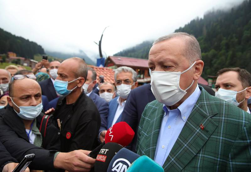 Turkey's President Recep Tayyip Erdogan wearing a face mask to protect against the spread of coronavirus, speaks to the media in Ayder village in the Black Sea city of Rize, Turkey, Sunday, Aug. 16, 2020. Turkey's health minister says the number of new COVID-19 infections Saturday has hit its highest in 45 days and announced 1,256 new cases.(Turkish Presidency via AP, Pool)