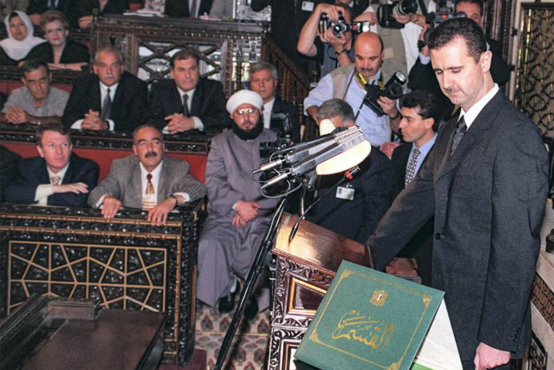 """(FILES) In this handout file photo provided by the Syrian Arab News Agency SANA on July 17, 2000, Syria's new President Bashar al-Assad (R) takes the oath of office at the Syrian parliament in the capital Damascus. - President Bashar al-Assad, whose family has ruled Syria for over half a century, faces an election this week meant to cement his image as the only hope for recovery in the war-battered country, analysts say. (Photo by - / SANA / AFP) / == RESTRICTED TO EDITORIAL USE - MANDATORY CREDIT """"AFP PHOTO / HO / SANA"""" - NO MARKETING NO ADVERTISING CAMPAIGNS - DISTRIBUTED AS A SERVICE TO CLIENTS =="""