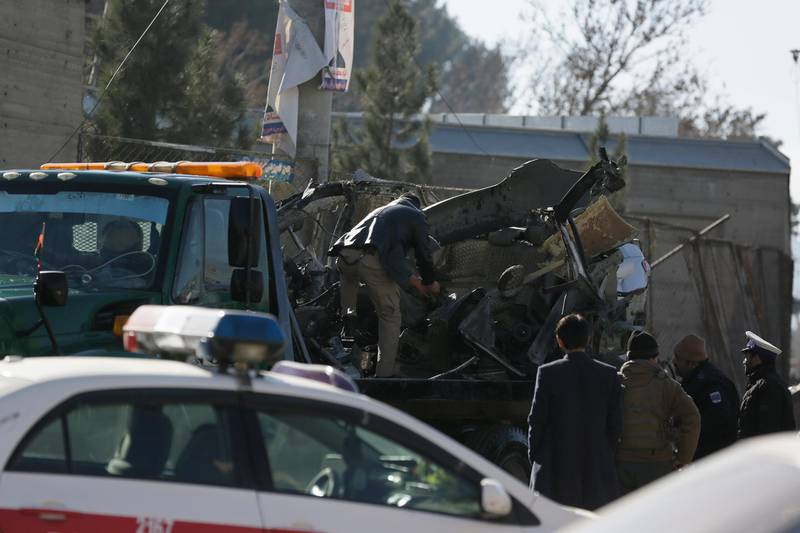 Afghan security personnel prepare to carry a damaged car which was used for a car bomb explosion in Kabul, Afghanistan, Thursday, Dec. 31, 2020. (AP Photo/Mariam Zuhaib)
