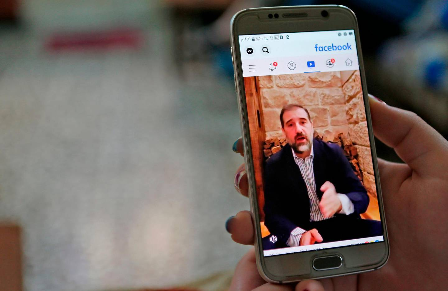 A woman watches the Facebook video of Syrian businessman Rami Makhlouf on her mobile in Syria's capital Damascus, on May 11, 2020. Syria's top tycoon publicly airing his grievances has revealed a power struggle within the ruling family as it tries to cement its power after nine years of war, analysts say. After years of staying out of the limelight, business magnate Rami Makhlouf this month in two videos on Facebook laid bare his struggles with the regime headed by his first cousin President Bashar al-Assad, in what analysts say is a desperate last stand. / AFP / -