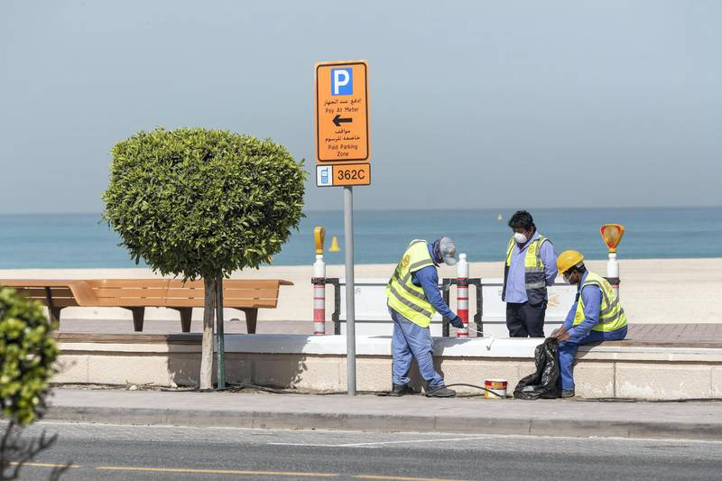 DUBAI, UNITED ARAB EMIRATES. 01 APRIL 2020. An empty Sunset Beach located between the Jumeirah Beach Hotel and Kite Beach with the ongoing Stay At Home policy being enforced on a National level in the UAE. Municipal workers paint a cement wall bench along the walking path while wearing masks. (Photo: Antonie Robertson/The National) Journalist: Standalone. Section: National..