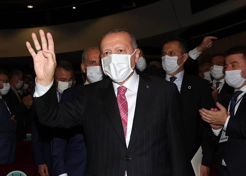 """A hand out image made available by the Turkish President Press service on August 13, 2020, shows the leader of Turkey's ruling Justice and Development (AK) Party, Turkish President Recep Tayyip Erdogan holds up his hand in the Rabia or Rabaa four finger sign as he greets the crowd during AK Party's extended meeting of provincial heads at the AK Party Headquarters in Ankara on August 13, 2020.    The 'Rabaa sign' became the symbol of protests at Rabaa al-Adawiya Square in Cairo against the 2013 ouster of Egypt's first democratically elected president Mohamed Morsi, of the Muslim Brotherhood. It has been adopted by Erdogan replacing the V-sign for victory. - RESTRICTED TO EDITORIAL USE - MANDATORY CREDIT """"AFP PHOTO /Turkish President Press service"""" - NO MARKETING - NO ADVERTISING CAMPAIGNS - DISTRIBUTED AS A SERVICE TO CLIENTS  / AFP / TURKISH PRESIDENTIAL PRESS SERVICE / Handout / RESTRICTED TO EDITORIAL USE - MANDATORY CREDIT """"AFP PHOTO /Turkish President Press service"""" - NO MARKETING - NO ADVERTISING CAMPAIGNS - DISTRIBUTED AS A SERVICE TO CLIENTS"""
