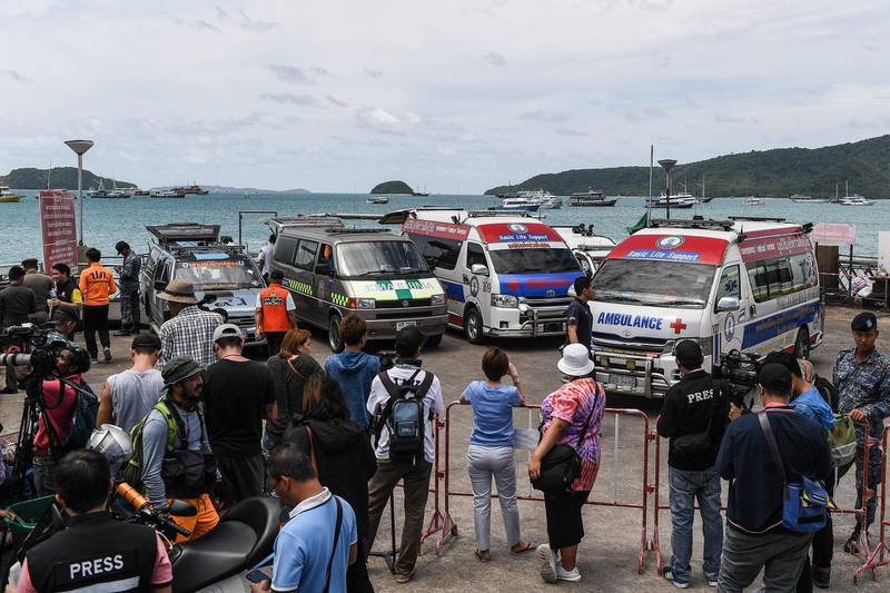 Ambulances are seen before recovered bodies of passengers from a capsized tourist boat arrive at Chalong pier in Phuket on July 6, 2018.   Dozens of passengers are missing after a boat capsized as high winds whipped up rough seas off the Thai tourist island of Phuket, officials said late July 5. / AFP / Mohd RASFAN