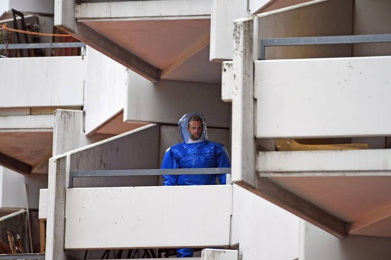 FILE - In this June 15, 2018 file photo a German police officer in protective gear walks down stairs in an apartment building at Osloerstrasse 3, in Cologne, Germany. Federal prosecutors say they have filed charges against a Tunisian suspect and his German wife who are accused of producing biological weapons for an attack in Germany. (Henning Kaiser/dpa via AP)