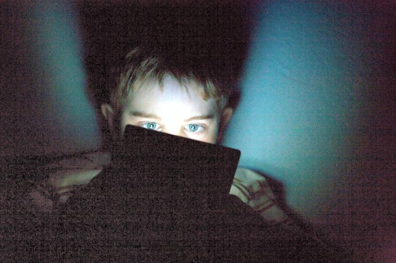 B7MA15 nine year old boy playing nintendo portable ds video game system in the dark, expressing great concentration