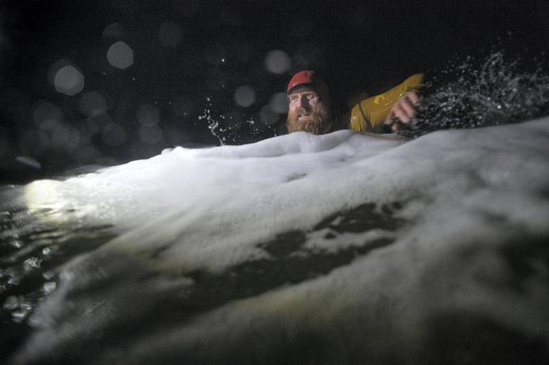 PORTRUSH, NORTHERN IRELAND - MARCH 01: Pro surfer Al Mennie swims through heavy surf at Downhill strand as he completes his 100KM night swim for charity on March 1, 2021 in Portrush, Northern Ireland. Pro big wave surfer Al Mennie has completed his Surf Swim Through The Darkness challenge of swimming 100KM in the dark throughout the winter months in the North Atlantic ocean to raise awareness of depression and funds for the Aware charity which promotes mental health awareness. (Photo by Charles McQuillan/Getty Images)