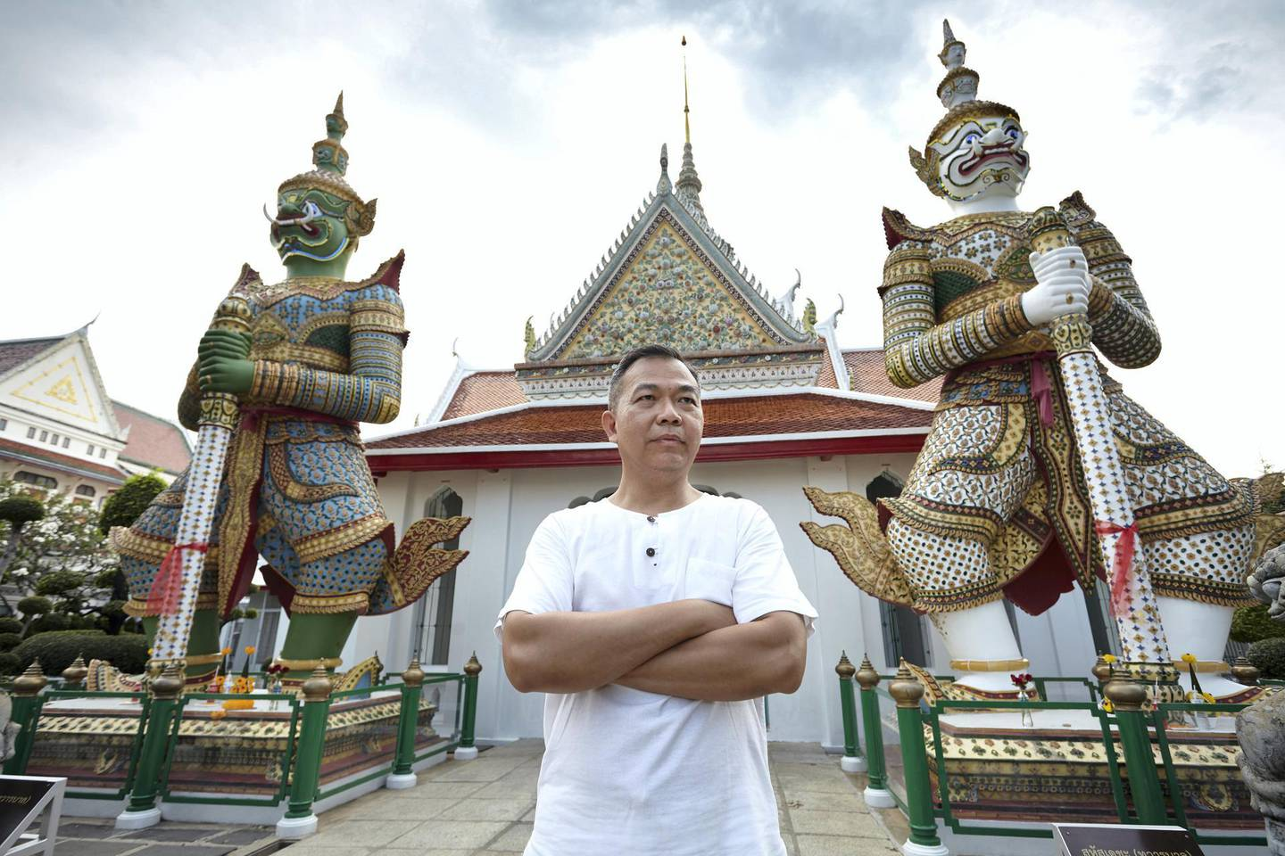 Bangkok-Thailand-Temple of dawn- Hartanto's Portrait, standing in front of the two famous Guardian Giant statues at Wat Arun (the Temple of dawn). Sasamon Rattanalangkarn for The National