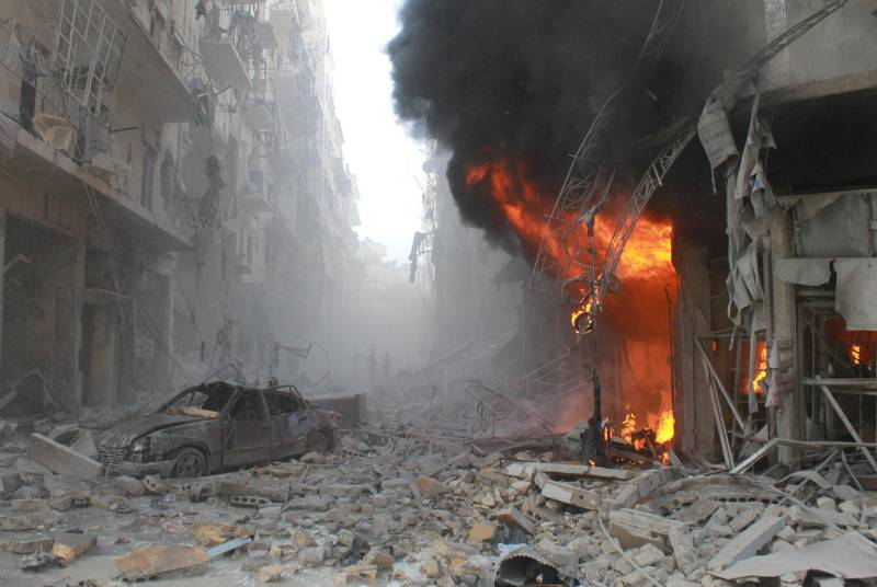 Debris cover a street and flames rise from a building following a reported air strike by Syrian government forces on March 7, 2014 during the Friday prayer in the Sukkari neighborhood of the northern city of Aleppo. More than 140,000 people have been killed in Syria since the start of a March 2011 uprising against the Assad family's 40-year rule. AFP PHOTO / BARAA AL-HALABI (Photo by BARAA AL-HALABI / AFP)