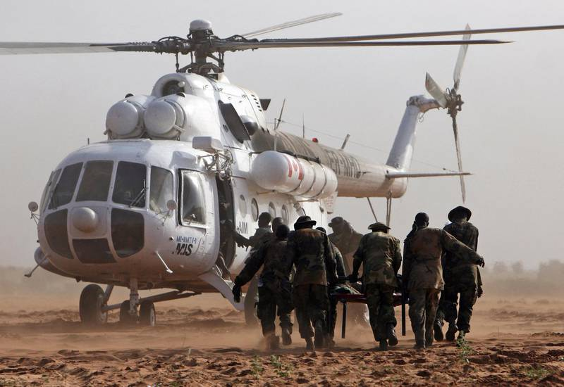 A handout picture from the African Union Mission in the Sudan (AMIS) shows AMIS soldiers carrying an injured colleague to an helicopter at Haskanita military group site (MGS) 30 September 2007 following an attack. The African Union began 01 October 2007 probing the unprecedented attack on one of its bases in Sudan's war-ravaged Darfur that left 10 peacekeepers dead and 25 missing, vowing to punish those responsible. The attack by a large, organised group of heavily armed men who overran southern Darfur's Haskanita camp in 30 vehicles took place 29 September night, the worst assault on the under-manned force since it deployed in July 2004. AFP PHOTO/HO/AMIS/STUART PRICE (Photo by STUART PRICE / AMIS / AFP)