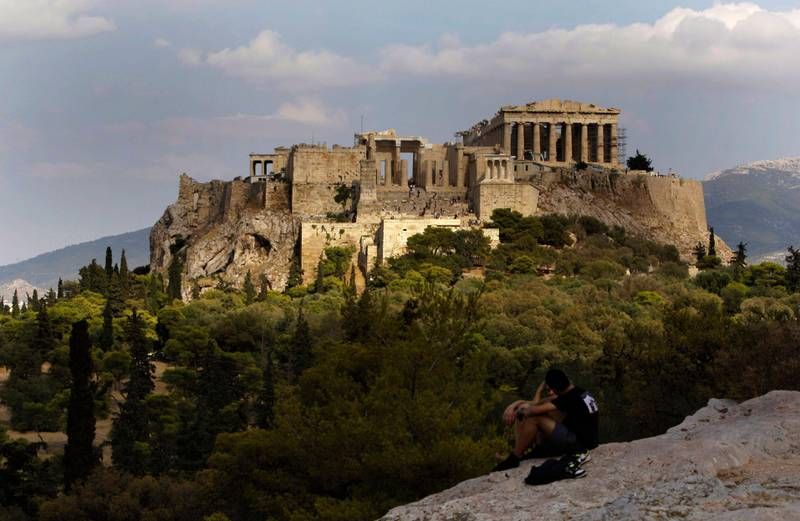 In this photo taken Sunday, Sept. 5, 2010, visitors sit on a rocky outcrop looking out onto the Acropolis, with the newly-restored temple of Athena Nike, distinguished by its four Ionic columns, on a platform below and to the left of the Parthenon, in Athens, Sunday, Sept. 5, 2010. A ten-year restoration project has just been completed on the 2,400-year-old temple, which was dismantled to ground level and rebuilt to correct damage from ground subsidence and rusting internal joints. (AP Photo/Petros Giannakouris) *** Local Caption ***  ATH103_Greece_Disappearing_Temple.jpg