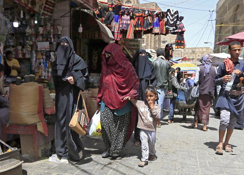 Yemeni women walk past shops in the old city market of the capital Sanaa, on March 2, 2020. - In recent months, a series of incidents in the rebel-held north illustrates the Huthis' determination to impose their own moral order on Yemenis who have already endured five years of grinding conflict: restaurants where men and women mingle have been shut down, scissor-wielding militia have policed men's hairstyles, and rebel forces have patrolled college campuses to enforce dress codes. (Photo by MOHAMMED HUWAIS / AFP)