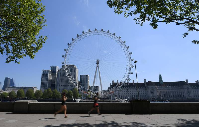 LONDON, ENGLAND - APRIL 26: The London Eye is seen from the Embankment  as runners go past on April 26, 2020 in London, England. The 40th London Marathon was due to take place today, with thousands of runners due to take part. It has postponed until October 04 due to the coronavirus (COVID-19) outbreak.  (Photo by Alex Davidson/Getty Images)