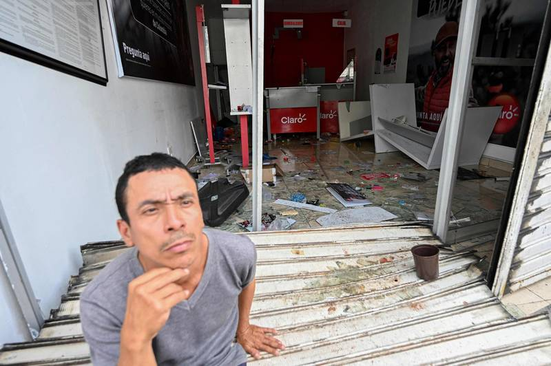 A man sits at the entrance of a store destroyed during clashes between demonstrators and riot police officers in the protests against the government's tax reform in Cali, Colombia, on May 4, 2021. The international community on Tuesday decried what the UN described as an 'excessive use of force' by security officers in Colombia after official data showed 19 people were killed and 846 injured during days of anti-government protests. / AFP / LUIS ROBAYO