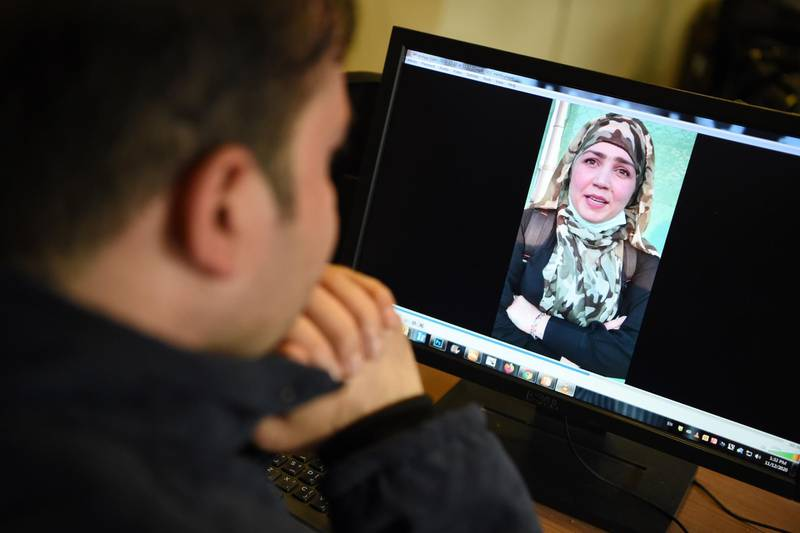 In this picture taken on November 12, 2020, a man watches a video of Afghan woman Muzghan, who walked free from jail in September after confessing to being members of the Taliban's ultra-violent Haqqani network, on a computer screen in Kabul. Female assassins who lured an Afghan security official to his death with promises of sex before shooting him and dumping his body at a cemetery are among thousands of Taliban criminals freed as part of a fragile peace plan. - TO GO WITH 'Afghanistan-conflict-Taliban-women-prisoners, FOCUS' by Elise BLANCHARD  / AFP / Wakil KOHSAR / TO GO WITH 'Afghanistan-conflict-Taliban-women-prisoners, FOCUS' by Elise BLANCHARD