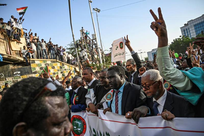 """Sudanese judges, dressed in their robes, gather for a """"million-strong"""" march outside the army headquarters in the capital Khartoum on April 25, 2019. - Sudanese protesters began gathering for a """"million-strong"""" march to turn up the heat on the ruling military council after three of its members resigned following talks on handing over power. (Photo by OZAN KOSE / AFP)"""