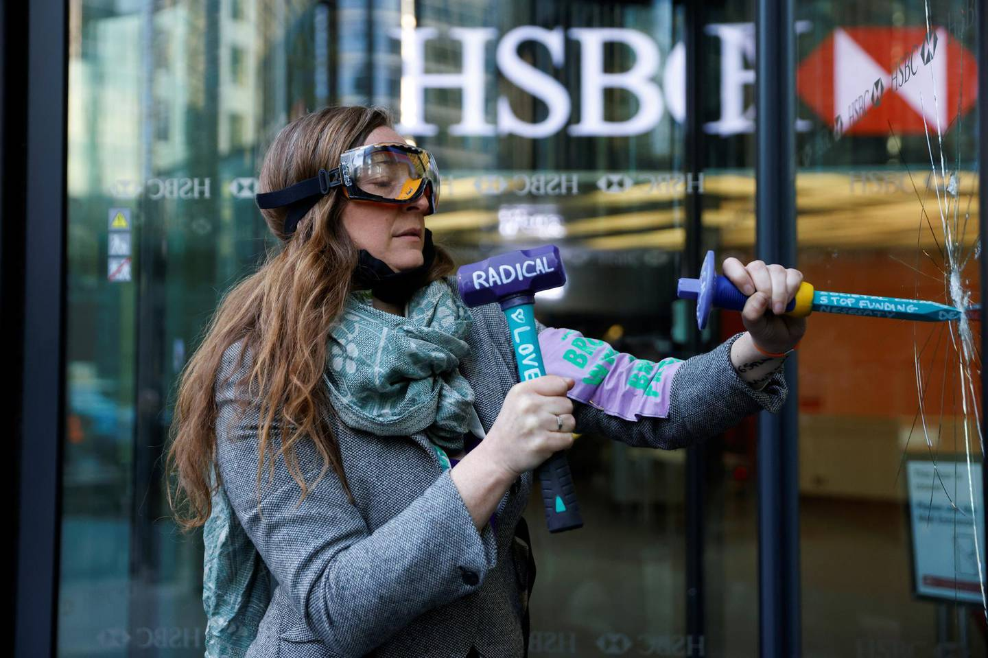An activist from the Extinction Rebellion, a global environmental movement, smashes a window at HSBC headquarters during a protest in Canary Wharf, London, Britain April 22, 2021. REUTERS/John Sibley