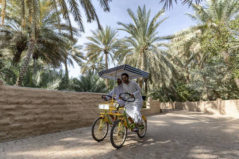 Al Ain, United Arab Emirates - Reporter: N/A: Two young men ride though Al Ain Oasis. Tuesday, December 17th, 2019. Al Ain Oasis, Al Ain. Chris Whiteoak / The National