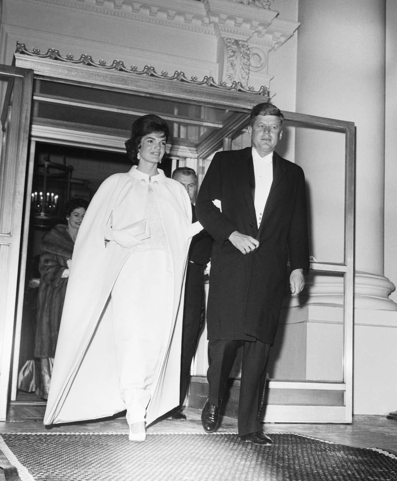 (Original Caption) 1/20/1961-Washington, D.C.: Full length shot of President and Mrs. John F. Kennedy as they left the White House to attend a series of inaugural balls. Five locations were booked to hold the tremendous crowd that wanted to attend. The First Lady's dress was designed by Oleg Cassini.
