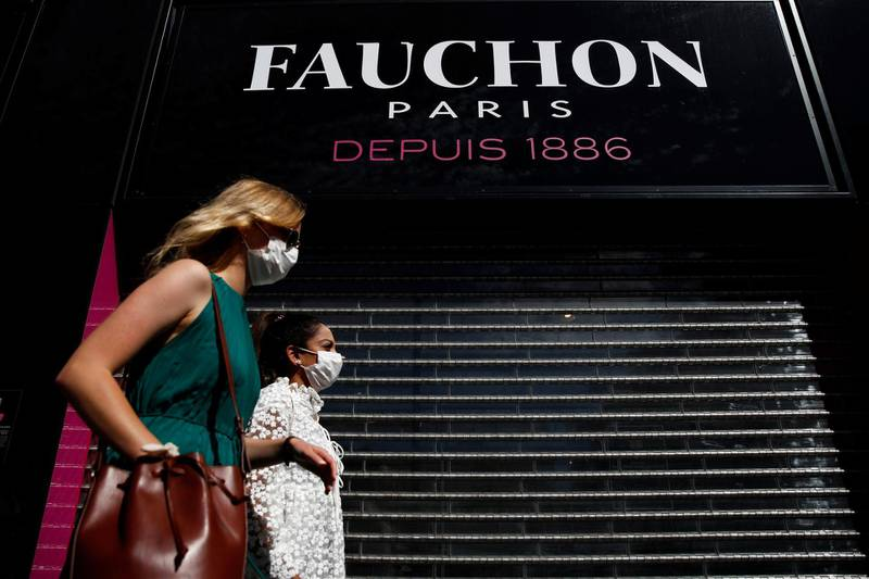 Women wearing protective face masks walk past a closed shop of French luxury foods group Fauchon on the Place de La Madeleine in Paris, France, September 4, 2020. REUTERS/Gonzalo Fuentes