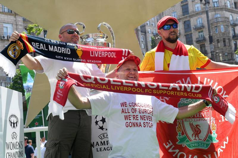 Liverpool fans pose in front of the UEFA Champions League Cup (C) on display at the fan zone in Kiev on May 24, 2018, ahead of the football match between Real Madrid and Liverpool FC next May 26 at the Olimpiyskiy Stadium.  / AFP / Sergei SUPINSKY