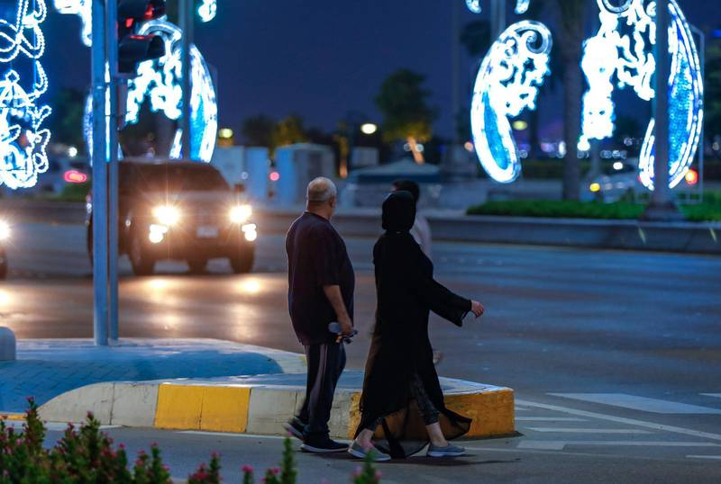 Abu Dhabi, United Arab Emirates, July 19, 2020.     Eid Al Adha Corniche lights.  A couple crosses the Corniche.Victor Besa  / The NationalSection: NAReporter:
