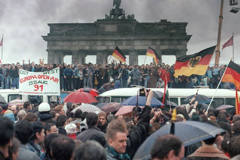 """People from East Germany and West Germany gather for the opening of the Brandenburg Gate in Berlin on December 22, 1989. On November 09, Gunter Schabowski, the East Berlin Communist party boss, declared that starting from midnight, East Germans would be free to leave the country, without permission, at any point along the border, including the crossing-points through the Wall in Berlin. The Berlin concrete wall was built by the East German government in August 1961 to seal off East Berlin from the part of the city occupied by the three main Western powers to prevent mass illegal immigration to the West. According to the """"August 13 Association"""" which specialises in the history of the Berlin Wall, at least 938 people - 255 in Berlin alone - died, shot by East German border guards, attempting to flee to West Berlin or West Germany. (Photo by PATRICK HERTZOG / AFP)"""