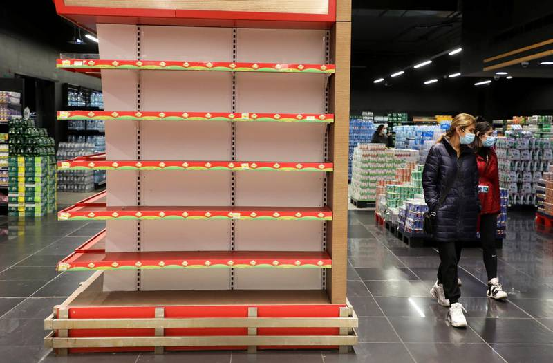 Shoppers walk past an empty shelf at a supermarket in Beirut, Lebanon March 16, 2021. Picture taken March 16, 2021. REUTERS/Mohamed Azakir
