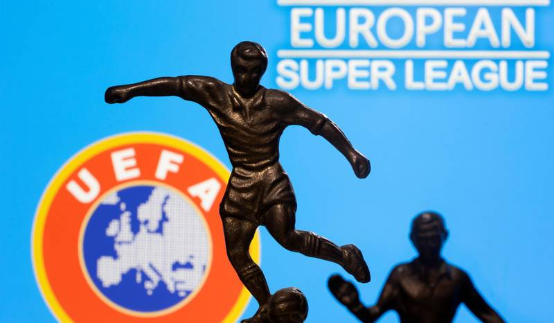 """FILE PHOTO: Metal figures of football players are seen in front of the words """"European Super League"""" and the UEFA logo in this illustration taken April 20, 2021. REUTERS/Dado Ruvic/Illustration/File Photo"""