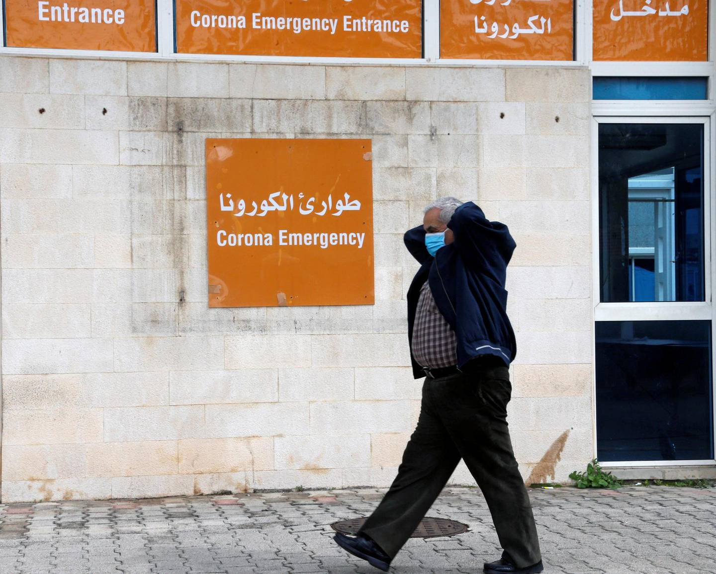 A man wears a face mask as he walks near the entrance of emergency at Rafik Hariri hospital, as Lebanon recorded its first death from coronavirus, in Beirut, Lebanon March 10, 2020. REUTERS/Mohamed Azakir