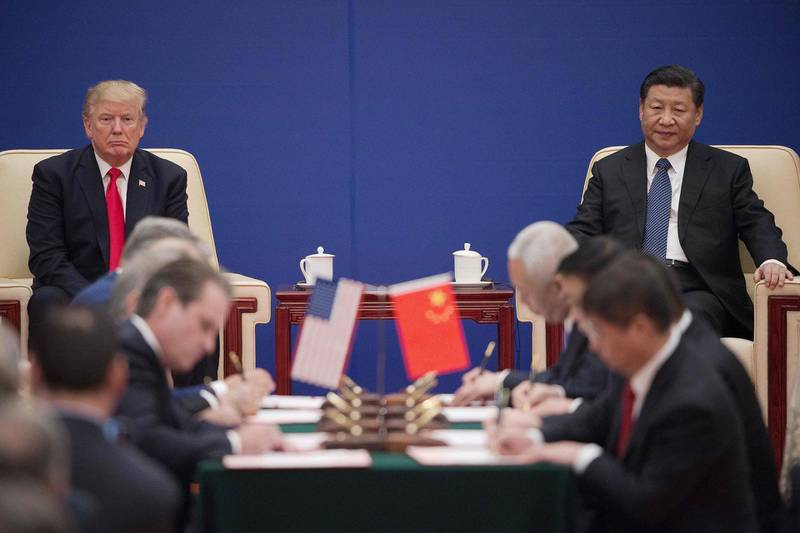 (FILES) This file photo taken on November 9, 2017 shows US President Donald Trump (L) and China's President Xi Jinping attending a business leaders event inside the Great Hall of the People in Beijing.  From remote Himalayan valleys to small tropical islands and tense Western capitals, an increasingly assertive China is taking on conflicts around the world like never before as the United States retreats.  - TO GO WITH AFP STORY CHINA-POLITICS-DIPLOMACY,FOCUS BY JING XUAN TENG  / AFP / Nicolas ASFOURI / TO GO WITH AFP STORY CHINA-POLITICS-DIPLOMACY,FOCUS BY JING XUAN TENG