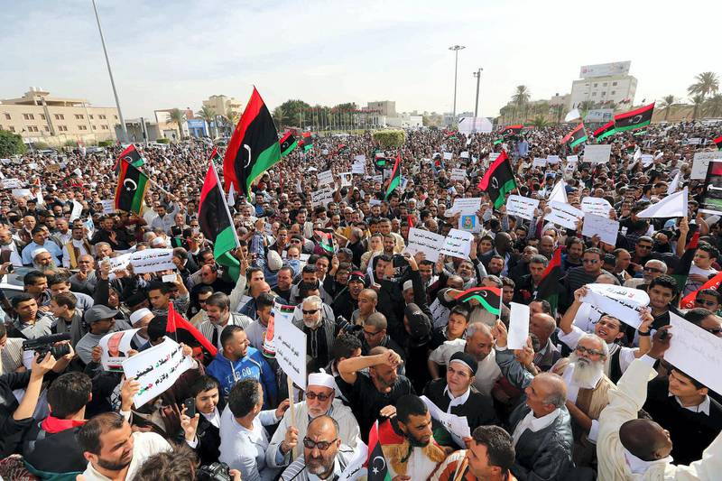Libyans demonstrate in a street in the capital Tripoli to demand the withdrawal of all  armed militias from the capital on November 22, 2013. Residents of Libya's capital were turning out Friday to press militias remaining in the city to follow others and withdraw, aiming to keep up the momentum following deadly clashes last weekend. Many of the groups have long rejected government calls to lay down their arms or integrate into the armed forces, triggering the frustration of Libyans who once hailed them as heroes for toppling Kadhafi. AFP PHOTO/MAHMUD TURKIA (Photo by MAHMUD TURKIA / AFP)