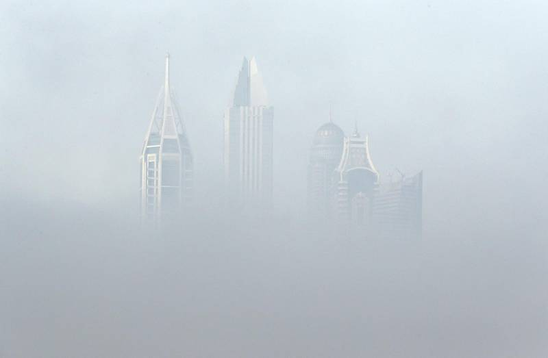 DUBAI, UNITED ARAB EMIRATES , April 08 – 2020 :- View of the towers in Dubai Media City during the early morning fog in Dubai. Dubai is conducting 24 hours sterilisation programme across all areas and communities in the Emirate and told residents to stay at home. UAE government told residents to wear face mask and gloves all the times outside the home whether they are showing symptoms of Covid-19 or not. (Pawan Singh/The National) For News/Online/Instagram/Standalone