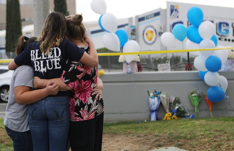 SANTA CLARITA, CALIFORNIA - NOVEMBER 15: A Saugus High School student (2nd L) is embraced as she visits a makeshift memorial in front of the school for victims of the shooting there on November 15, 2019 in Santa Clarita, California. The shooting left two students dead and others wounded while a suspect in the shooting is being treated at a local hospital for a gunshot wound to the head.   Mario Tama/Getty Images/AFP == FOR NEWSPAPERS, INTERNET, TELCOS & TELEVISION USE ONLY ==