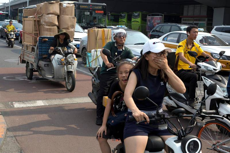 A delivery man transports goods on the streets of Beijing, China, Friday, July 6, 2018. The United States hiked tariffs on Chinese imports Friday and Beijing said it immediately retaliated in a dispute between the world's two biggest economies that President Donald Trump says he is prepared to escalate. (AP Photo/Ng Han Guan)