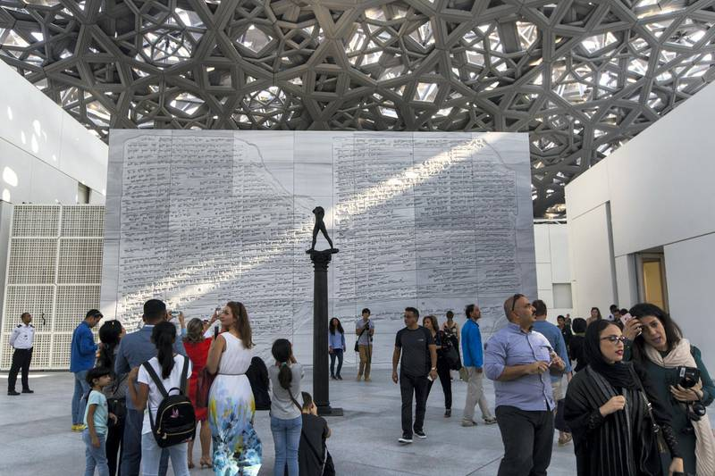 Abu Dhabi, United Arab Emirates, November 11, 2017:    Visitors walk past the Walking Man, On a Column sculpture by artist Augusta Rodin on the opening day at the Louvre Abu Dhabi on Saadiyat Island in Abu Dhabi on November 11, 2017. Christopher Pike / The National  Reporter: James Langton, John Dennehy Section: News